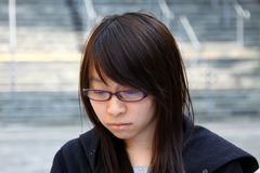Chinese girl with sad face. A typical Chinese girl shows her sad face, she is a student on campus, probably because of the academic result Stock Photography