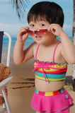 Chinese girl on the sand beach. With bear and Three-point swimsuit Stock Photography