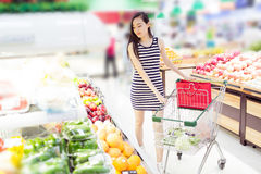 Chinese girl in the selection of fruit Stock Photos