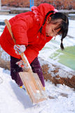 Chinese girl shoveling snow Royalty Free Stock Photos