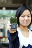 A Chinese girl showing her cell phone. She is a business woman to show her smart phone to all people Stock Photo