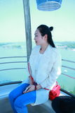 A Chinese girl sits in Ferris wheel. Blue jeans, long hair, red bag, white T-shit, over look of luo ma lake in city of Su Qian Royalty Free Stock Photography
