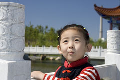 Chinese girl with smile. The Chinese girl looking up to see her mother.This photo was taken with chinese gloriette and bridge Stock Photo