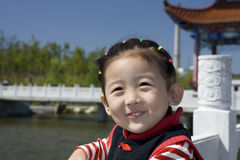 Chinese girl with smile. The Chinese girl looking up to see her mother.This photo was taken with chinese gloriette and bridge Stock Photos