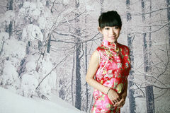 Chinese girl in the snow scenes. A Chinese girl in traditional dress is on the snow scenes background Royalty Free Stock Photo
