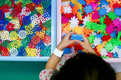 Chinese girl solving puzzle. An Asian Chinese girl solving puzzle at indoor playground royalty free stock photo
