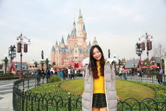 A Chinese girl stand in front of Disney Castle in Shanghai of China Stock Images