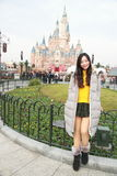 A Chinese girl stand in front of Disney Castle in Shanghai of China Royalty Free Stock Image
