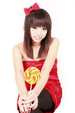 Chinese girl with sweet candy. Happy Chinese girl with sweet candy sitting on white background Royalty Free Stock Photos
