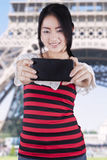 Chinese girl taking picture at Eiffel Tower Stock Photography