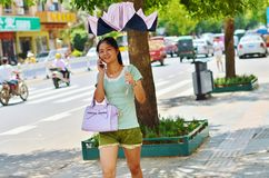 Chinese girl talking on the phone protected. From the sun by a canopy Royalty Free Stock Photo