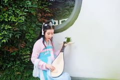 Chinese girl in traditional ancient drama costume hanfu cosplay play flute guitar pipa. Chinese beauty in traditional ancient costume, hold a fan on hand Stock Images