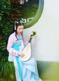 Chinese girl in traditional ancient drama costume hanfu cosplay play flute guitar pipa. Chinese beauty in traditional ancient costume, hold a fan on hand Stock Photography
