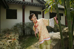A Chinese girl in traditional dress. A beautiful girl in Chinese ancient dress is in the park Stock Image