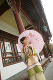 A Chinese girl in traditional dress. A beautiful girl in Chinese ancient dress is in the park Stock Images