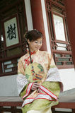 A Chinese girl in traditional dress. A beautiful girl in Chinese ancient dress is in the park Stock Photos