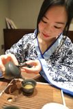Tea art of China,pour tea. A Chinese girl in traditional dress blue hanfu is performing tea art. China has history of tea culture for more than one thousand Royalty Free Stock Photo
