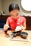 Tea art of China,make tea. A Chinese girl in traditional dress Red cheongsam is performing tea art. China has history of tea culture for more than one thousand Royalty Free Stock Photo
