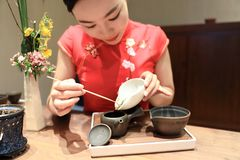 Tea art of China,make tea. A Chinese girl in traditional dress Red cheongsam is performing tea art. China has history of tea culture for more than one thousand Stock Image