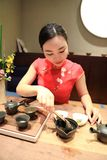 Tea art of China,pour tea. A Chinese girl in traditional dress Red cheongsam is performing tea art. China has history of tea culture for more than one thousand Stock Images