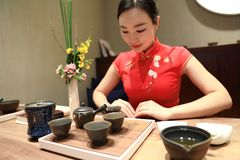Tea art of China,pour tea. A Chinese girl in traditional dress Red cheongsam is performing tea art. China has history of tea culture for more than one thousand Stock Photo