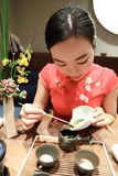 Tea art of China,pour tea. A Chinese girl in traditional dress Red cheongsam is performing tea art. China has history of tea culture for more than one thousand Royalty Free Stock Photos
