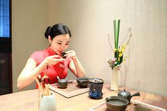 Tea art of China. A Chinese girl in traditional dress Red cheongsam is performing tea art. China has history of tea culture for more than one thousand years Royalty Free Stock Photos