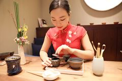 Tea art of China. A Chinese girl in traditional dress Red cheongsam is performing tea art. China has history of tea culture for more than one thousand years Royalty Free Stock Photo