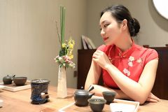 Tea art of China. A Chinese girl in traditional dress Red cheongsam is performing tea art. China has history of tea culture for more than one thousand years Royalty Free Stock Image