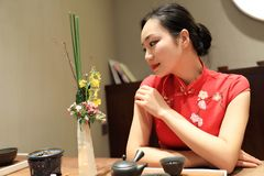 Tea art of China. A Chinese girl in traditional dress Red cheongsam is performing tea art. China has history of tea culture for more than one thousand years Royalty Free Stock Photography