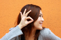A Chinese girl who is hearing the voice. She is an Asian and trying to use her hands to pretend listening to the others. It was taken in an orange background Stock Photography