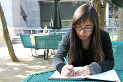 Chinese girl who is reading books. A Chinese girl who is a student, reading books on campus. She is studying hard for exam Stock Image