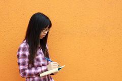 Chinese girl who is reading books. A Chinese girl who is a student, reading books and writing notes. She is studying hard for exam Royalty Free Stock Photography