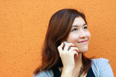 Chinese girl who is talking in phone. This girl is so busy in talking by phone, with smile on the face under orange background Royalty Free Stock Photo
