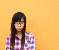 A Chinese girl who is very sad. It is isolated on orange background Royalty Free Stock Photo