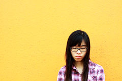 A Chinese girl who is very sad. It is isolated on orange background Stock Photography