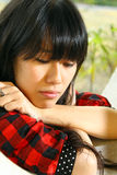 A Chinese girl who is very sad. She is depressed and standing in a window. She is an asian and very young Royalty Free Stock Images