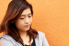 A Chinese girl who is very sad. She is depressed and standing next to a orange wall, thinking her future Royalty Free Stock Images