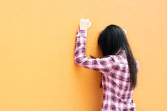 A Chinese girl who is very sad. She is depressed and facing the orange wall Stock Images