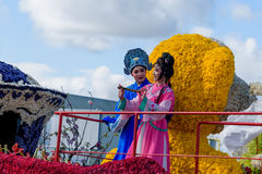 Chinese girl and young man in native clothes on a boat from flowers. Famous event. Stock Images