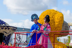 Chinese girl and young man in native clothes on a boat from flowers. Parade Stock Photo