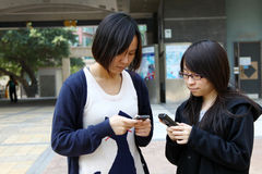 Chinese girls who are concentrating on phone Royalty Free Stock Photo