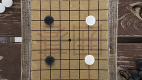 Chinese Go or Weiqi board game. Black and white stones and hand made small board. Opening position Royalty Free Stock Photo