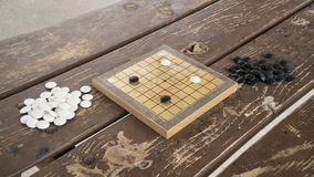 Chinese Go or Weiqi board game. Black and white stones and hand made small board. Opening position Stock Photos