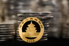 Chinese Gold Coin with Piles of Silver Coins. This Chinese Gold Coin has piles of Silver Coins in the background stock photo