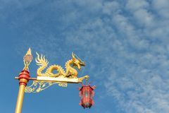 Gold dragon on the pole with the red lantern. The Chinese gold dragon on the pole with the red lantern with sky background Stock Photos