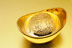 Chinese gold ingot. Close up of chinese gold ingot over golden background royalty free stock photo