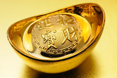 Chinese gold ingot. Close up of chinese gold ingot over golden background stock photos