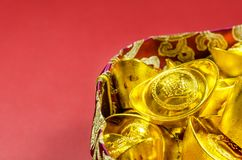 Chinese gold ingots with red pouch  on red background. Chinese gold ingots English translation for foreign text means blessing,rich and luck with red pouch  on Royalty Free Stock Photos