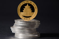 Chinese Gold Pand Coin on top of Silver Coins Stock Image